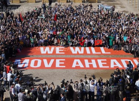 Hundreds of government and civil society supporters of the Paris Agreement pose together at the COP22 in Marrakech with a giant banner bearing the words 'We Will Move Ahead' to show their determination to move ahead with action against climate change in the wake of the US election.