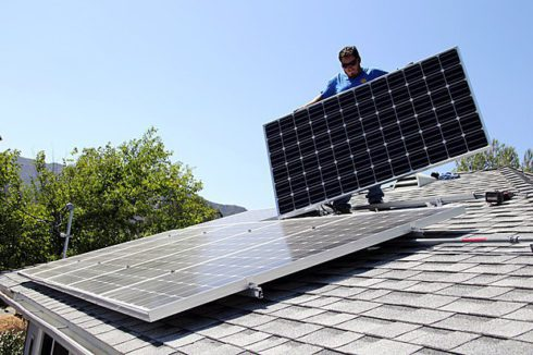 Работник Miracle Solar устанавливает солнечные батареи на доме, штат Калифорния, США, 5 августа 2016 года.